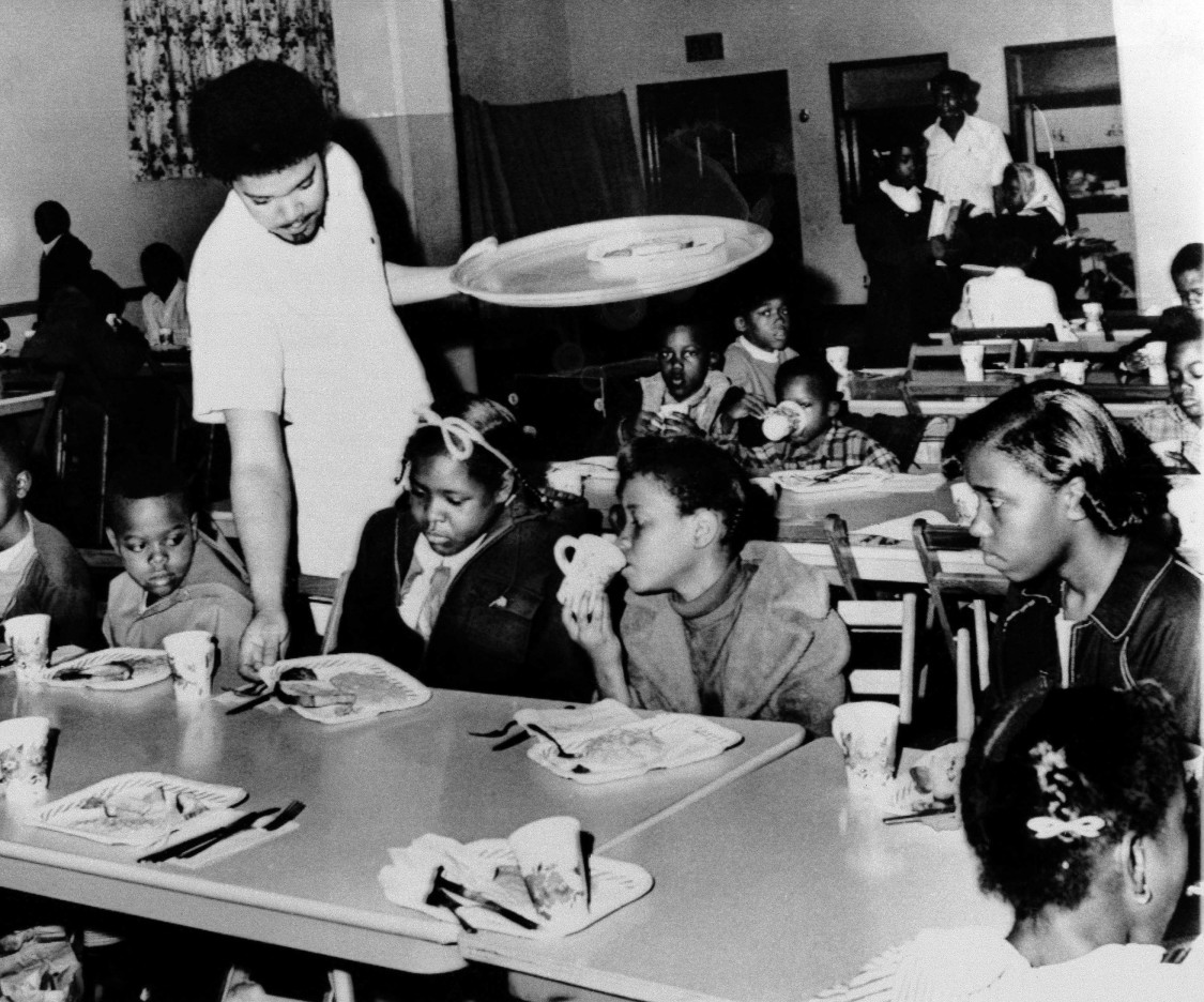 Bill Whitfield, member of the Black Panther chapter in Kansas City, serves free breakfast to children before they go to school, April 16, 1969. Merchants have supplied food and money for the daily meals. The panthers are a radical Black Power group whose members in some cities have been charged with violent activities. The Kansas City Panthers say that they keep guns only for defense. (AP Photo/William P. Straeter)